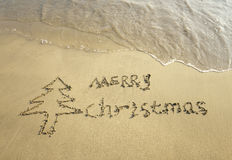 Merry Christmas written on tropical beach white sand with snowman Stock Image