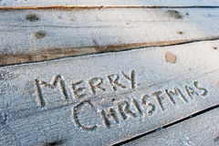 Merry Christmas written on a wooden background with frosts Royalty Free Stock Photography