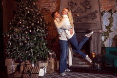 Merry Christmas. Young couple celebrating New Year at home. Man and woman hugging Stock Photos