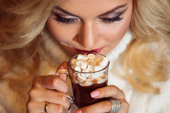 Merry Christmas. Young woman dressed warmly, drinking hot chocolate. Royalty Free Stock Photography