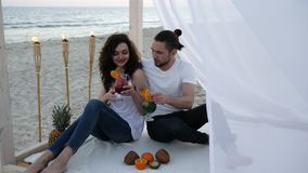Merry couple with cocktails, have fun, wind develops white cloth, bungalow, an exotic vacation, on background tropical. Fruits, burning torches and ocean coast stock video footage