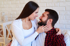Merry couple looking deeply into each others eyes while sitting royalty free stock image