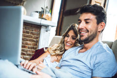 Merry couple on sofa with laptop Stock Photography