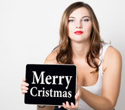 Merry cristmas written on virtual screen. beautiful woman with bare shoulders holding pc tablet. technology, internet Royalty Free Stock Photo
