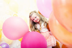 Merry curly girl posing with colorful balloons Stock Image