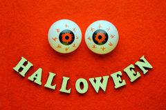 The word HALLOWEEN in the form of a smile and two balls of eye on a bright orange background. The inscription is made of wooden le stock photo