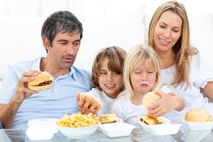 Merry family eating hamburgers Stock Image