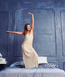 Merry female in a long nightgown standing with raised hand on th. Full-length shot of a merry female in a long nightgown standing with raised hand on the bed Royalty Free Stock Image
