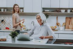Merry female is watching her mother with notebook in kitchen stock photography