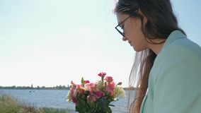 Merry florist woman in sunglasses collects beautiful bouquet of pink flowers on nature. Close up stock video footage