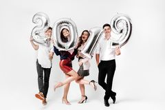 Merry friends two girls and two guys dressed in stylish clothes are holding balloons in the shape of numbers 2019 on a royalty free stock photo