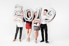 Merry friends two girls and two guys dressed in stylish clothes are holding balloons in the shape of numbers 2019 on a royalty free stock image