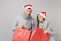 Merry fun couple girl guy in red Santa Christmas hat gray sweaters scarves isolated on grey wall background, studio stock images