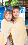 A merry girl and boy are wrapped in a towel. Stand on a background a pool Royalty Free Stock Photo
