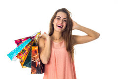 Merry girl holds in his hand a lot of bright packages with purchases and put her  on my head isolated  white background Royalty Free Stock Photography