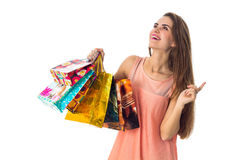 Merry girl looks up and holding a colorful shopping bags isolated on white background Royalty Free Stock Photography