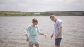 The merry girl runs along the water in the river. Romance, youth and a honeymoon. Lovers Boy and girl hugging in water. The guy and the girl have fun in the stock footage