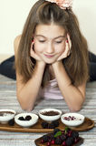 Merry girl with sweet dessert and berries in porcelain bowls Stock Images