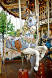 Merry Go Round Amusement Ride Old Carousel Horse. Vintage carved wood nostalgic carousel riding horse with antique painted decor mounted on a classic brass pole Stock Photo