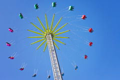 Merry-go-round, chain swing carousel ride in amusement park. Shot from below, blue sky Royalty Free Stock Photo