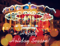 Merry-Go-Round illuminated at night. New year greeting on background with blurred carousel and bokeh. Merry Christmas and Happy Ne Royalty Free Stock Photography