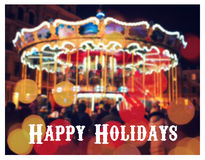 Merry-Go-Round illuminated at night. New year greeting on background with blurred carousel and bokeh. Merry Christmas and Happy Ne Stock Photography