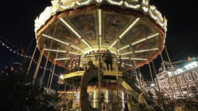 Merry Go Round at Night. Dolly shot of beautiful colorful vintage Merry go round at Christmas fair at night stock footage