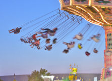 Merry-go-Round. Riders on a Merry-go-Round are swung through the air from suspended chairs during the 2014 Wisconsin State Fair Royalty Free Stock Photo