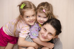 Merry and happy children and a mother embracing look in the frame Royalty Free Stock Photos