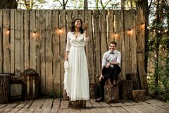 Merry happy young couple have fun near a wooden installation. royalty free stock photography