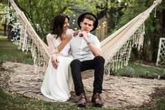 Merry happy young couple hugging in a hammock. Closeup. Royalty Free Stock Photos