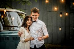 Merry happy young couple hugging near a retro minivan. Close-up. Merry happy young couple hugging near a retro minivan. Close-up stock photos