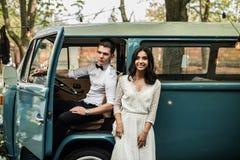 Merry happy young couple near a retro minivan. Close-up. Merry happy young couple near a retro minivan. Close-up stock photo