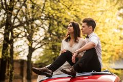 Merry happy young couple sit on the roof of the car. Close-up. royalty free stock photos