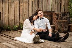 Merry happy young couple sitting on the wooden floor. Closeup. Stock Images