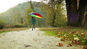 Merry little boy jumps with pied umbrella in autumn park
