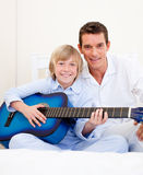 Merry little boy playing guitar with his father Royalty Free Stock Image