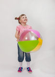 Merry little girl with a big ball. On neutral background Royalty Free Stock Image