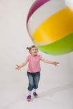 Merry little girl with a big ball. On neutral background Stock Photos