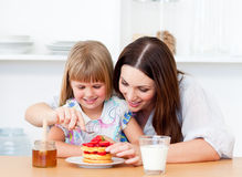 Merry little girl and her mother having breakfast Stock Photos