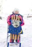 Merry little girl holding her winter sled Royalty Free Stock Image