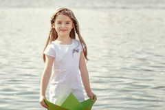Merry little girl posing with homemade paper boat Stock Photography