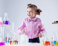 Merry little girl posing with variety of flasks Stock Images