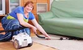 Merry mature woman vacuuming Stock Image