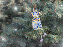 Merry monkey from clay pottery sits on the tree among the stars. Stock Photo