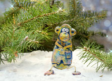 Merry monkey sits under the tree in the snow Stock Photography