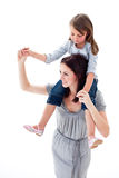 Merry mother giving her daughter piggyback ride Stock Image