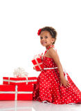 Merry mulatto girl with curly hair and red gift boxes. Royalty Free Stock Photo