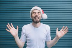 Merry and nice guy is showing his hands and fingers on camera. He is keeping eyes closed. Guy wears christmas hat. He is stock photo