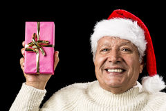 Merry Old Man Showcasing A Pink Wrapped Present. Upbeat smiling male senior lifting up an oblong present wrapped in pink and decorated with golden bowknot Royalty Free Stock Image